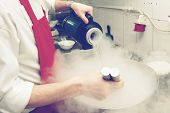 Chef is cooking ice cream with liquid nitrogen, toned image