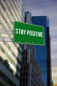 The word stay positive and green billboard sign against low angle view of skyscrapers