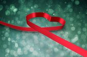 Red ribbon heart against blue abstract light spot design