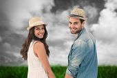 Happy hipster couple holding hands and smiling at camera against green grass under grey sky