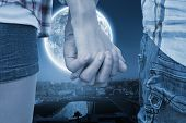 Couple in check shirts and denim holding hands against large moon over paris