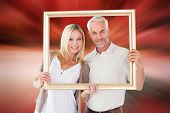 Happy couple holding a picture frame against large rock overlooking red sky