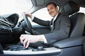 stock photo of driver  - Smiling businessman in the drivers seat in his car - JPG