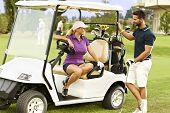 Golfers flirting in the fairway in golf cart, smiling.