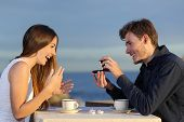 pic of sweethearts  - Boyfriend requesting hand of his girlfriend with a engagement ring in a restaurant with the ocean in the background - JPG