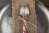Silverware tied with rope on burlap cloth and metal tray on wooden planks background