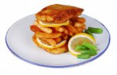 Breaded fried fillet and potatoes with asparagus and sliced lemon on plate isolated on white