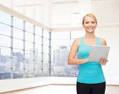 fitness, technology, people and sport concept - smiling woman with tablet pc computer over gym or home background