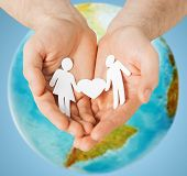 people, population, charity and love concept - close up of human hands holding paper couple with heart shape over earth globe and blue background