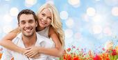 holiday, valentine's day, dating and love concept - happy couple having fun over blue lights and poppy field background