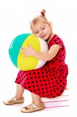 Dreaming little girl blonde with big inflatable ball sitting on