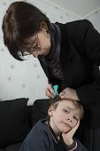 picture of lice  - Mother checking childs head for lice with a comb - JPG