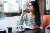 picture of woman  - Portrait of young beautiful woman using her mobile phone in coffee - JPG