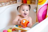 stock photo of bubble-bath  - funny toddler baby smiling while taking a bath - JPG