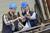 stock photo of mechanical engineering  - Engineer with mechanical worker checking on production - JPG