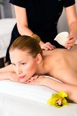 foto of oil well  - Woman in wellness beauty spa having back massage with essential oil - JPG
