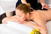 Woman in wellness beauty spa having hot stone massage, looking relaxed