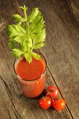 Tomato juice with celery branch on a wooden background