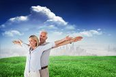 Happy couple standing with arms outstretched against sunny day by the river
