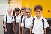 Cute schoolchildren smiling at camera by the school bus outside the elementary school