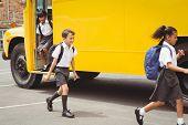Cute schoolchildren getting off the school bus outside the elementary school