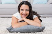 Pretty brunette lying on the rug at home in the living room