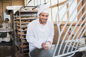 pic of mixer  - Smiling baker preparing dough in industrial mixer at the bakery - JPG