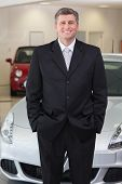 Smiling businessman standing with hands in pockets at new car showroom