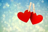 Hearts hanging on line against blue abstract light spot design