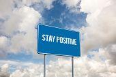 The word stay positive and blue billboard sign against blue sky with white clouds