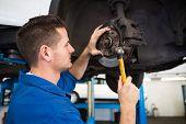Focused mechanic adjusting the wheel at the repair garage