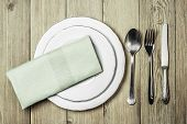 A white plate, a spoon, a fork, a knife and a green napkin dining room  on a wooden background