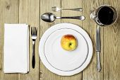 Plates with an apple, cutlery set, a napkin dining room and a wine glass on a wooden background