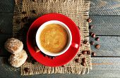 Cup of coffee and tasty cookies on sackcloth napkin, on wooden background