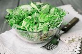 Cress salad with sliced cucumber and greens in glass bowl with fork and napkin on wooden planks background