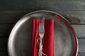 Silverware tied with rope on red napkin and metal tray background