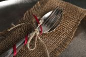 Silverware tied with rope on burlap cloth and metal tray background
