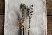 Silverware tied with rope on white fabric with dried flower on wooden planks background