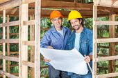 Portrait of confident male construction workers with blueprint in wooden cabin at site