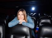 Mid adult woman leaning on seat while watching film at movie theater