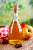 picture of cider apples  - Apple cider in glass bottle with cinnamon sticks and fresh apples on cutting board - JPG