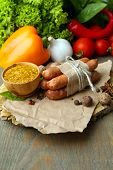 Composition of thin sausages, mustard in bowl and spices on cutting board, on wooden background