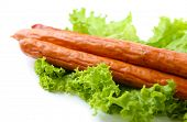 Smoked thin sausages  with lettuce salad leaves, isolated on white