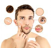 Handsome young man applying cream lotion on face isolated on white