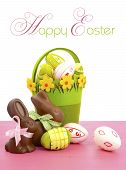 Happy Easter Chocolate Bunny Rabbits With Basket Of Pink, White And Green Eggs On Vintage Pink Wood