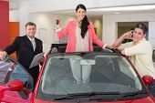 Woman standing in red cabriolet while holding her car key at new car showroom