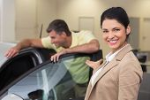 Businesswoman presenting a car to a client at new car showroom