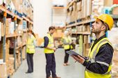 picture of warehouse  - Focused warehouse manager writing on clipboard in a large warehouse - JPG
