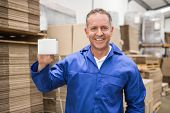 Smiling warehouse worker holding small box in a large warehouse