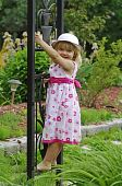 Little blond girl playing in garden